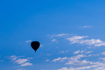 silhouetted: A hot air balloon is silhouetted against a bright blue sky. Stock Photo