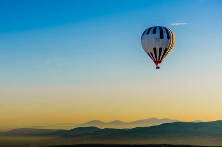 Hot air balloon flying overv olcanic rock landscape, Cappadocia, Turkey Stock Photo