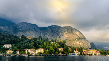 View of village with halo light in forest in Lake Como from ferry at sunset, Lake Como, Italy