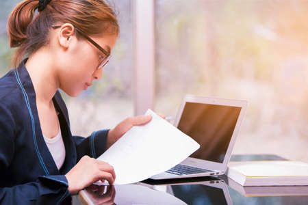 Asian office woman holding paper and looking write paper, business woman working in office and considering story in paper, beautiful worker standing and reading paper Stock Photo