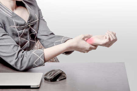 office woman pain at right wrist, case woman woking at table and pain at right wrist because of hard work, office syndrome concept