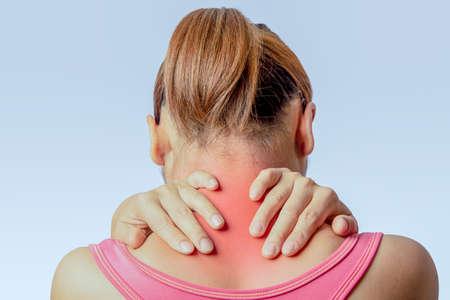 Mujer asiática sosteniendo la mano y tocando la piel alrededor de la columna cervical sobre fondo claro