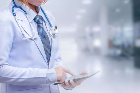 smart woman doctor holding tablet and pointing to screen on blurry out patient department of hospital, conception of modern medical with technology and data conection for early diagnosis Stock Photo