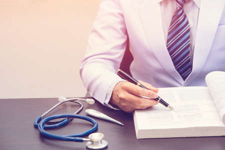smart doctor siting and reading book, doctor holding black pen and pointing to text book, medical concept