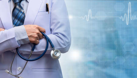 woman doctor crossed arm and holding stethoscope on blurred out patient department, medical concept, smart doctor with illustration ecg and medical equipment, medical concept Stock Photo