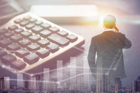 Doppelbelichtungsgeschäftsmann, der Smartphone mit großem Gebäude in Großstadt und Taschenrechner, Geschäftskonzept steht und benutzt Standard-Bild