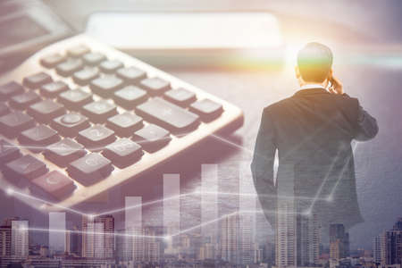 double exposure business man standing and using smart phone with big building in big city and calculator, business concept Stock Photo