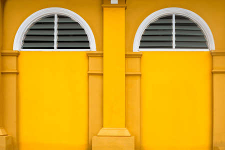 yellow building wall, yellow building and haft circle window