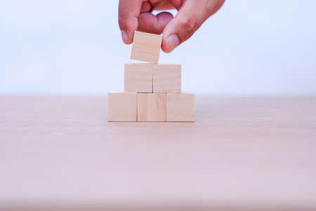 hand holding and arranging wood block stacking as step stair with space for your content in wooden block Stock fotó