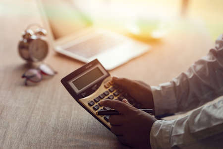 businessman with hand holding pen working on calculator to calculate business information data