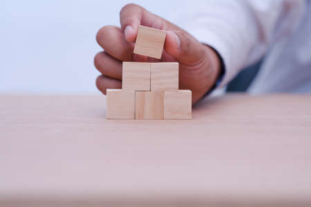 hand holding and arranging wood block stacking as step stair with space for your content in wooden block