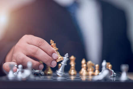 Business man holding golden king chess to finish game Stockfoto