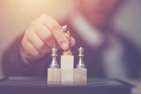 Business man holding golden king chess to winner position on wooden cube of the chess game Stockfoto