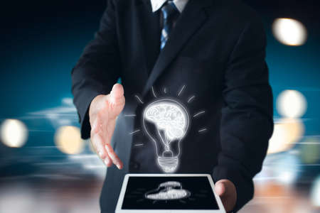 business man holding hand with drawing brain in bulb