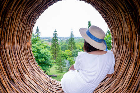 Woman sitting in circles sofa with pine trees view 版權商用圖片