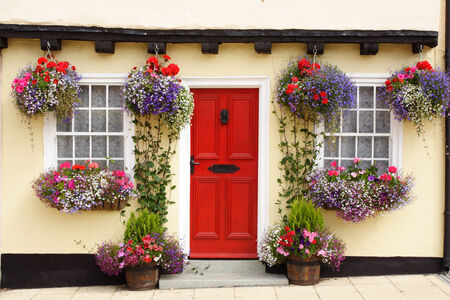 A Tudor cottage, with a beam and bright red door, has colourful hanging baskets and window boxes  photo