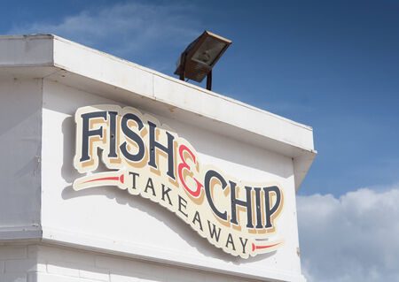Fish and chip takeaway shop sign, on a white building, against a blue sky  Copyspace in sky