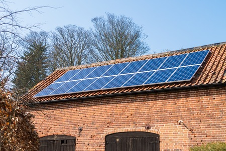 A group of solar panels on the roof of a farm building photo