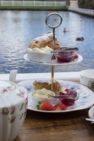 Traditional English afternoon tea, with a copy of tea and scones with jam, cream and strawberries at Southwold Boating Lake, Suffolk. photo