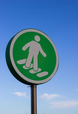 pedestrian crossing: A green pedestrian crossing sign in a supermarket car park.