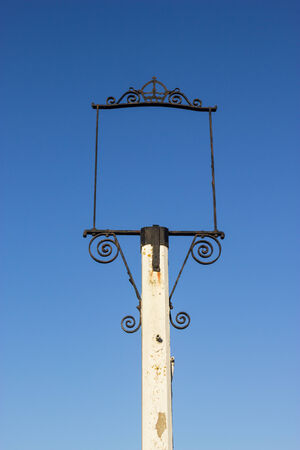 previously: An empty sign, with scrolled metal work on a white post, previously a public-house sign.