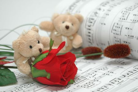 four friends: bear with musical score as background Stock Photo