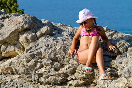 Girl 8 years with white hat and glasses sitting on the rocks by the sea photo