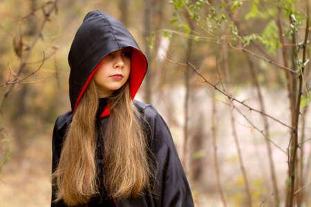숲에서 빨간색과 검은 망토의 소녀