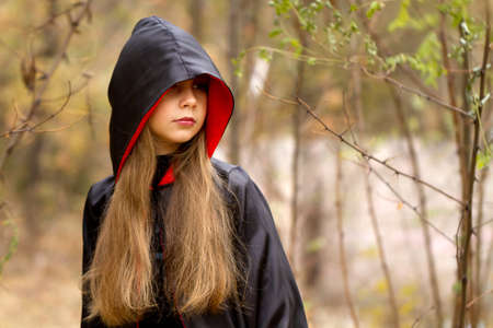 The girl in a red and black cape in the forest