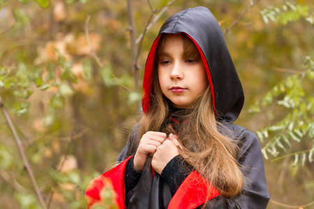 fairyland: The girl in a red and black cape in the forest