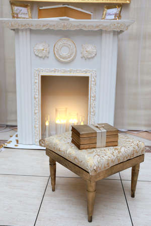 pouf: Three golden books on the pouf near the hearth