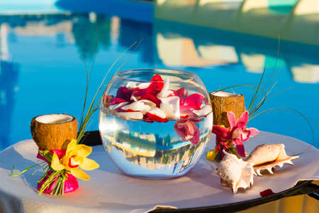 two glasses of coconut with orchids, two seashells and rose petals in a fishbowl photo