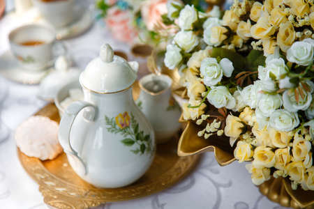 Flowers, ceramic teapot, marshmallows on a tray on the table photo