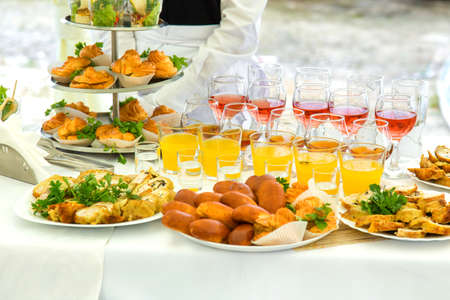 Pies, eclairs and drinks on a banquet table photo