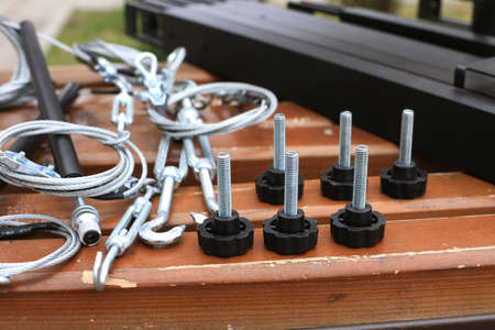 Bolts, fastening, hooks, rope lying on a wooden bench photo