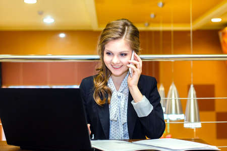 Young smiling girl sitting in a cafe with a laptop and talking on cell phone photo