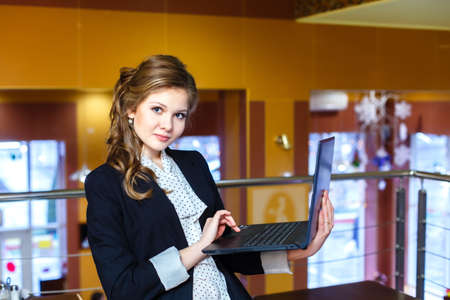 young beautiful girl standing in a cafe and working on laptop photo