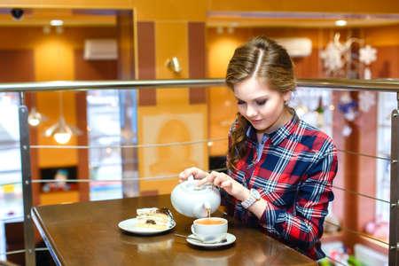 chemise carreaux: Les jeunes femmes dans une chemise � carreaux verse le th� vert