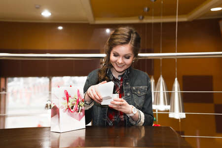 joyfully: Beautiful girl in the cafe opens and joyfully looks in a white gift box