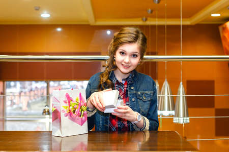 uncovering: Beautiful girl in the cafe opens a white gift box