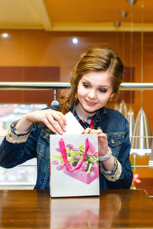 uncovering: Beautiful girl in a cafe pulled out a white gift box