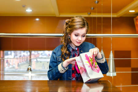 uncovering: Beautiful girl in a cafe looking in gift bag