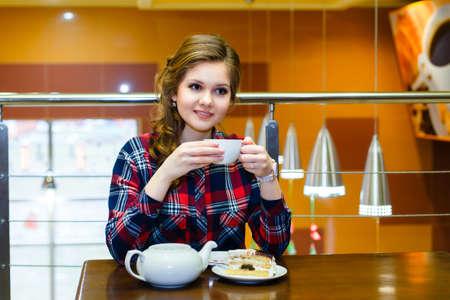chemise carreaux: r�fl�chie belle jeune fille dans un th� shirt potable carreaux dans un caf�