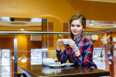 chemise carreaux: Jeune fille agr�able dans un th� shirt potable carreaux dans un caf�
