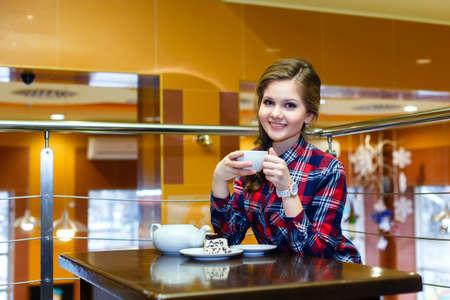 chemise carreaux: Sourire belle jeune fille dans un th� potable plaid shirt dans un caf�
