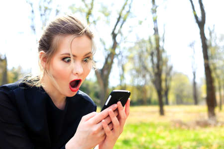 Girl with disheveled hair and open mouth stares into the smartphone