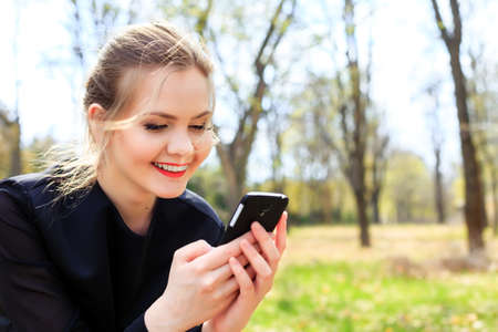 Woman with unkempt hair looking into smartphone smiling Stock Photo