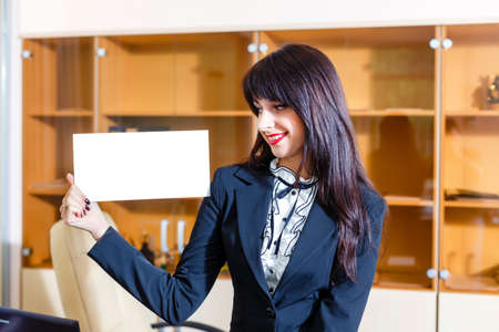 Beautiful woman with empty card in office