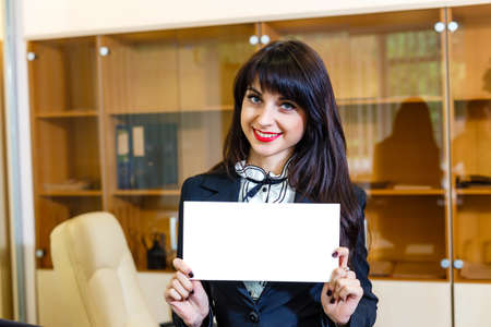 notecard: Beautiful smiling girl with empty card in office