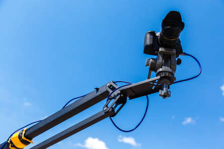Camera on a crane on a blue sky background